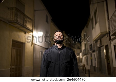 Bearded hipster man with tracksuit walking in the street - stock photo
