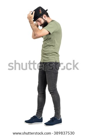 Bearded hipster walking and putting black hat with feather. Side view. Full body length portrait isolated over white studio background.