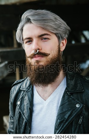Bearded hipster with nose ring in leather jacket  - stock photo