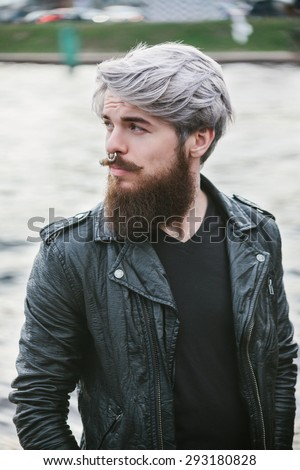 Bearded hipster with nose ring in leather jacket outdoor