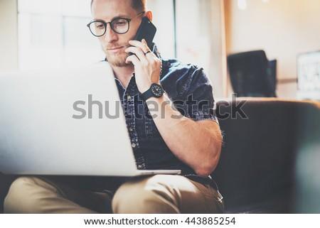 Bearded Hipster Working Laptop Modern Interior Design Loft Office.Intelligent Man Sitting Vintage Sofa.Using contemporary Smartphone Hand.Blurred Background.Creative Business Startup Process Idea.Film - stock photo