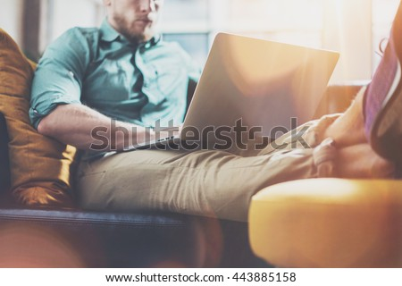 Bearded Hipster working Laptop modern Interior Design Loft Office.Man Work Coworking Studio,Use contemporary Notebook,Typing Message.Blurred Background.Creative Business Startup Idea.Flares effect - stock photo