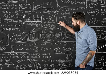 Bearded hipster writes formulas on a chalkboard - stock photo