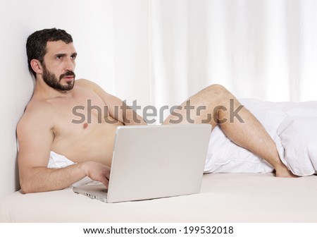 bearded latin man in bed with laptop - stock photo