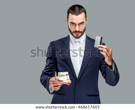 Bearded male in a suit holding cash money isolated on grey background.