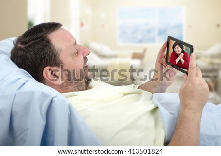 Bearded male patient lying on hospital bed has video chat with happy woman on phone. This hospital offers free wireless internet access Wi-Fi. Horizontal indoors shot. - stock photo