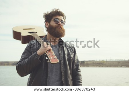 Bearded man and guitar, near river