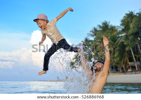 Bearded man and his cute gallant son in bright slim fit shirt, dark pants and fedora hat. Boy is jumping from dad's hands. They are both in water - wet, fooling around happily making splashes