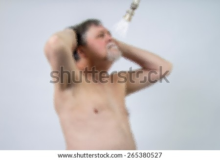 Bearded man behind frosted glass in shower lathering up his hair with shampoo