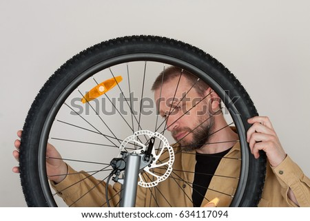 Bearded man checks the fastening of the front wheel with hydraulic disc brake on the mtb bicycle.