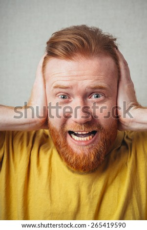 bearded man closed his ears with his hands - stock photo