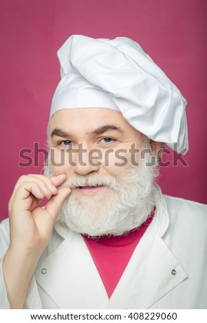 Bearded man cook in chef hat closeup in studio on pink background