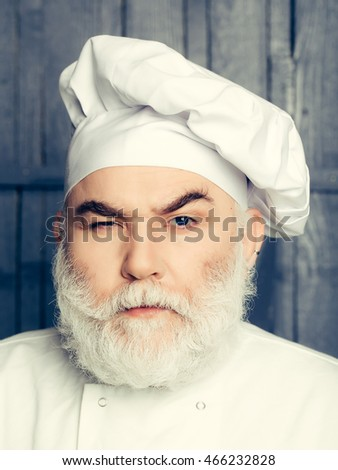 Bearded man cook in chef hat closeup in studio on wooden background