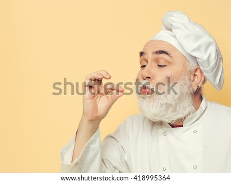Bearded man cook in chef hat with fingers near mouth in studio on yellow background