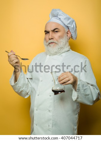 Bearded man cook in studio preparing food with sauce on yellow background