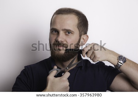 Bearded man cut his beard with scissors and comb