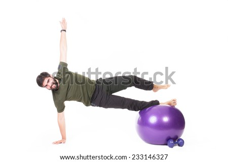 Bearded man doing aerobics on purple fitness ball - isolated on white.