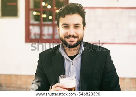 Bearded man drinking beer with suit in outdoors bar terrace