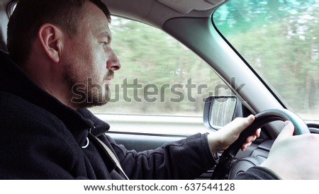 Bearded man drives a car on a highway road. View from the passenger seat.