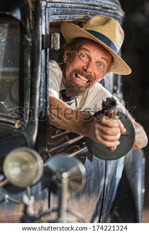 Bearded man firing submachine gun from vintage 1920s car - stock photo