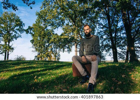 Bearded man hipster with vintage retro suitcase in summer park