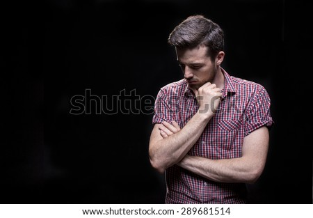 Bearded man holding his hand on his chin against black background in a purple T-shirt - stock photo