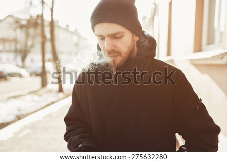 Bearded man in a hat smoking a cigarette on the street