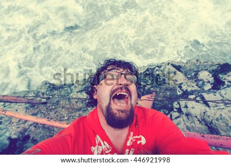 Bearded man in a red shirt and sunglasses, frightened cries falling from a cliff. Toned - stock photo