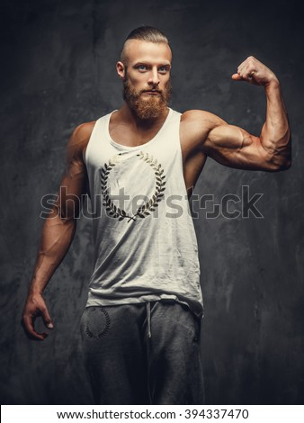 Bearded man in a white t shirt showing his biceps. - stock photo