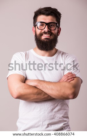 Bearded man in glasses with crossed hands look at camera on white - stock photo