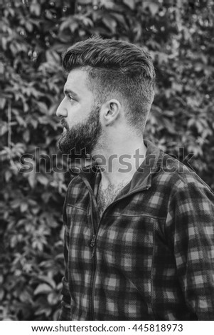 bearded man in nature, green background