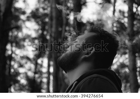 bearded man in the woods Smoking a cigar, brooding - stock photo