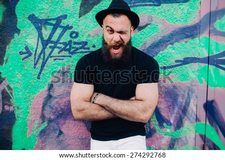 bearded man is a macho, posing near wall with graffiti - stock photo