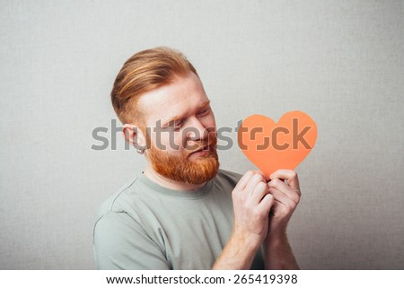 bearded man is happy and keeps the heart in the hands