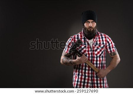 Bearded man like woodcutter holding an old axe - stock photo