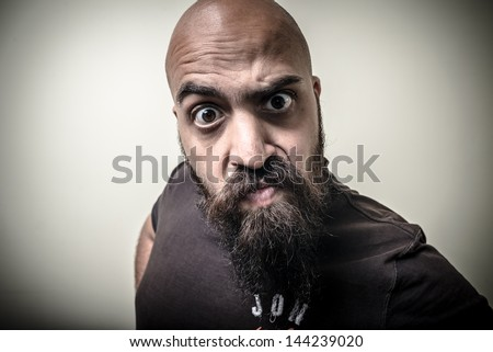 bearded man looking camera with funny strange expression on gray background - stock photo