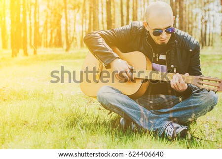 Bearded man playing guitar outdoors