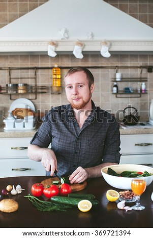 bearded man preparing vegetarian salad in the kitchen - stock photo