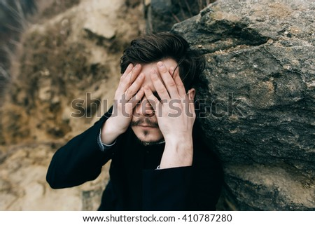 bearded man priest or pastor in mountains closed the face hands. anonymous - stock photo