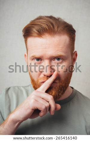 bearded man put his finger to his lips - stock photo