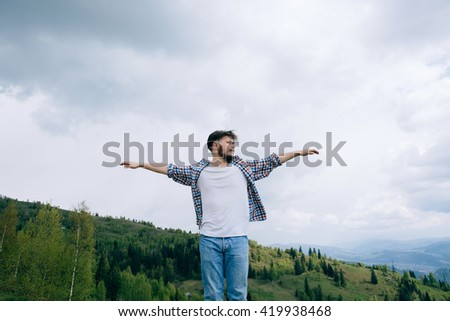 Bearded man raised his hands up in mountains, Freedom - stock photo