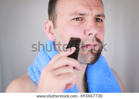 bearded man shaving electric