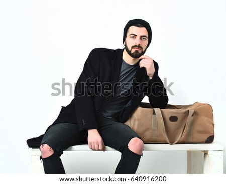 Bearded man, short beard. Caucasian hipster with moustache, leaning on stylish bag, wearing black jacket and ripped jeans, isolated on white background