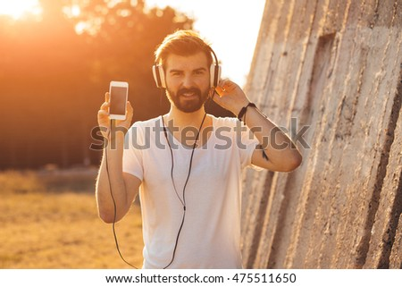Bearded man showing his music list on smart phone