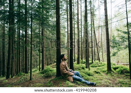 bearded man sits dream in mountain green forest  - stock photo