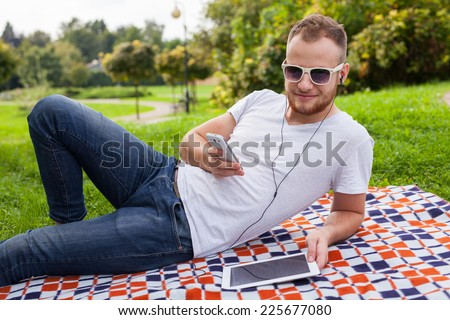 Bearded man sitting in park on blanket. He is using mobile phone. Outdoor photo. He looks relaxed - stock photo