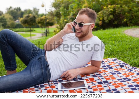 Bearded man sitting in park on blanket. He is using mobile phone. Outdoor photo. He looks relaxed
