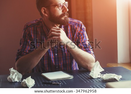 Bearded man sitting near blank copy book and thinking - stock photo