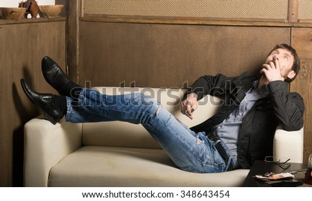 bearded man sitting on a couch and smoking a cigar