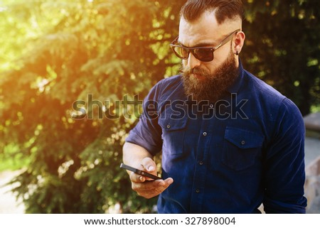 bearded man stands on the street and speaks by phone - stock photo